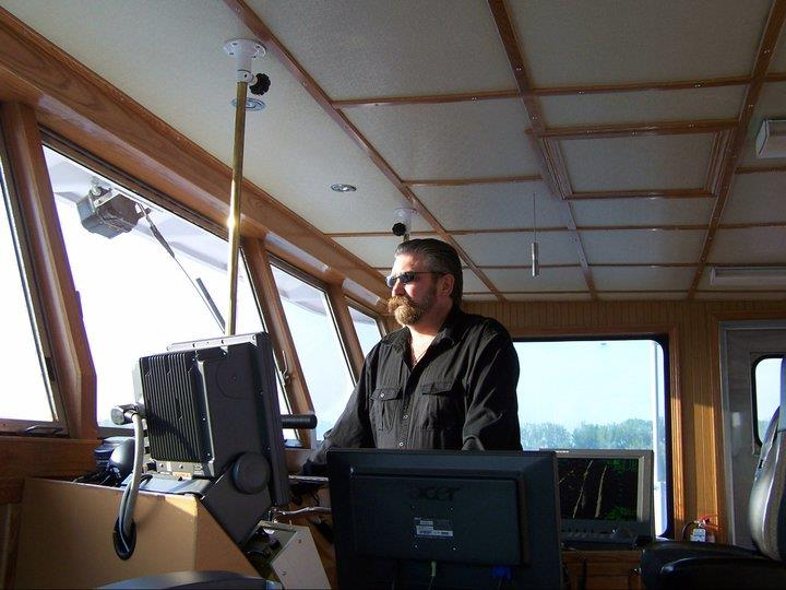 Barge captain piloting tugboat